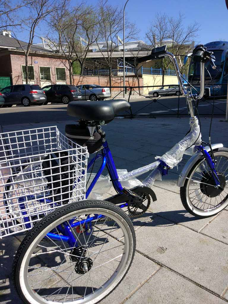 Un triciclo con motor de 500 W en rueda delantera y la batería en el portabultos.