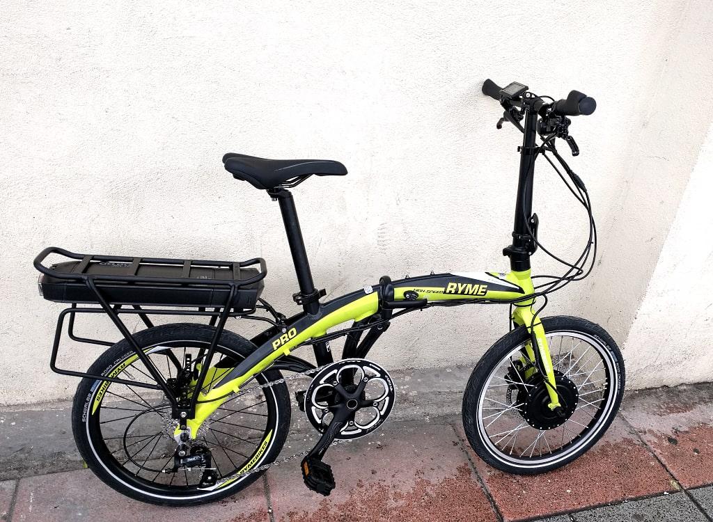 Una opción que solemos recomendar para bicicletas plegables es ubicar la batería en un transportín. De esta manera se conserva la capacidad de plegado de la bicicleta. Esta llamativa RYME lleva un motor de 250 W en la rueda trasera y la batería en un útil portabultos. La batería tiene una capacidad de 11 Ah que permitirá unos 80 Km de ayuda en nivel medio. El portabultos incluido en el kit es de calidad y soporta hasta 25 kg de carga. La batería lleva luz trasera incorporada, y el controlador del motor está alojado en el soporte de la batería, para un montaje muy limpio y estético.