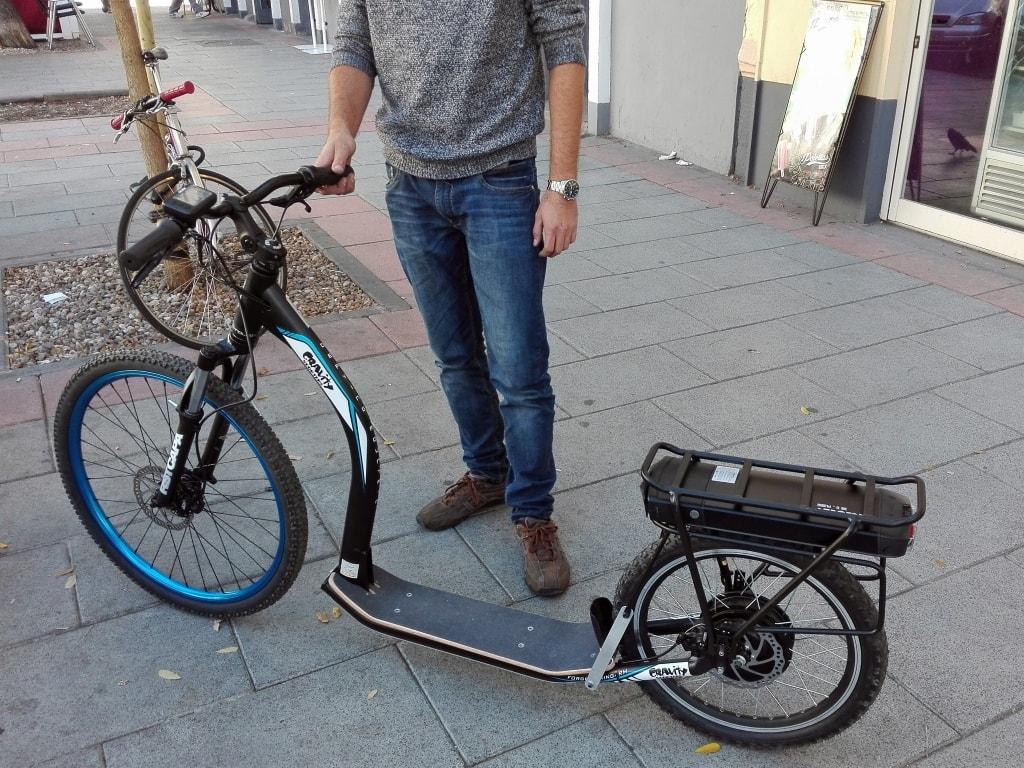 Este patinete lleva un motor trasero de 500 W y la batería en un transportín. Como no puede llevar sensor de pedaleo se acciona con un acelerador de puño, como una moto.